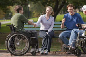 A Young man in a wheelchair talking to a young woman on a park bench holding her hand and another man on the bench is talking to a man in a wheelchair beside him